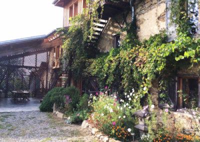 L'extérieur de la maison rénovée écologiquement et recouverte de végétation et de fleurs